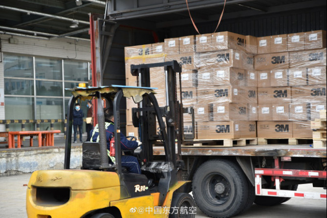 A Chinese worker loads masks donated by Shanghai to South Korea's Daegu and Gyeongsangbuk-do, March 2. A total of 500,000 pieces of masks are donated. (Photo courtesy of China Eastern Airlines' page on Weibo)