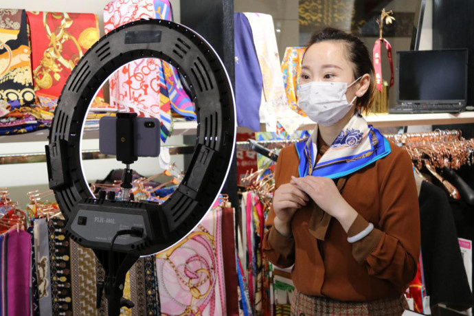 A merchant hosts a livestreaming show to sell her products on Xiushui Street, a shopping center in Chaoyang district, Beijing, March 3, 2020. The shopping center reopened to business on the same day. Liu Jing/People's Daily Online