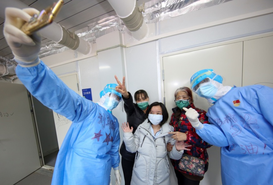 Recovered patients pose for a picture with medical workers before leaving the Huoshenshan Hospital, March 14. Photo by Liu Yibo, People's Daily Online
