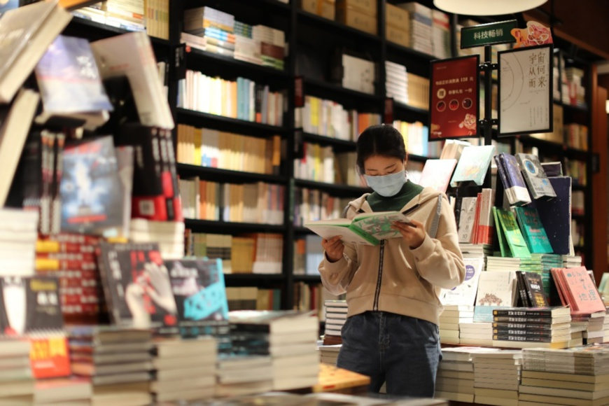 A woman in southwest China's Chongqing municipality reads a book in a bookstore, March 18, 2020. With continuous efforts to maintain strict epidemic prevention and control measures while promoting resumption of work and production, brick-and-mortar bookstores in Chongqing have resumed business one after another. Some bookstores in the city have rolled out book delivery services to better meet the demands of consumers. (Photo by Sun Kaifang/People's Daily Online)