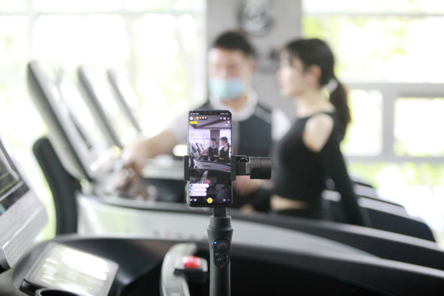 A fitness trainer and a trainee livestream a fitness course at a gym in Yangzhou, East China's Jiangsu Province, April 23. (Photo by Meng Delong/People's Daily Online)