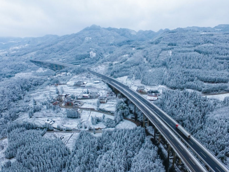 Photo shows the G76 Xiamen–Chengdu Expressway spanning the Wumeng Mountain range blanketed with white snow. (Photo by Li Xin, People's Daily Online)
