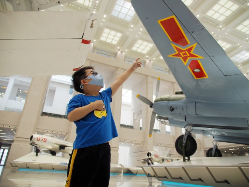A boy observes helicopters exhibited in the Military Museum of the Chinese People's Revolution, May 6, 2020. (Photo by Du Jianpo/People's Daily Online)