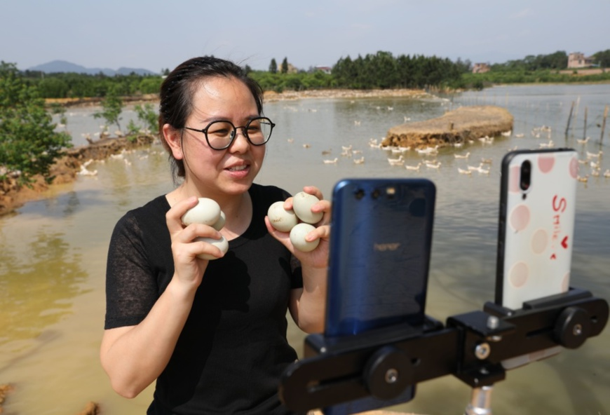 An online salesperson of an e-commerce company introduces duck eggs to customers through online streaming in Shangdu village, Xianglinpu township, Daoxian county in central China's Hunan province on May 5. Photo by He Hongfu/People's Daily Online