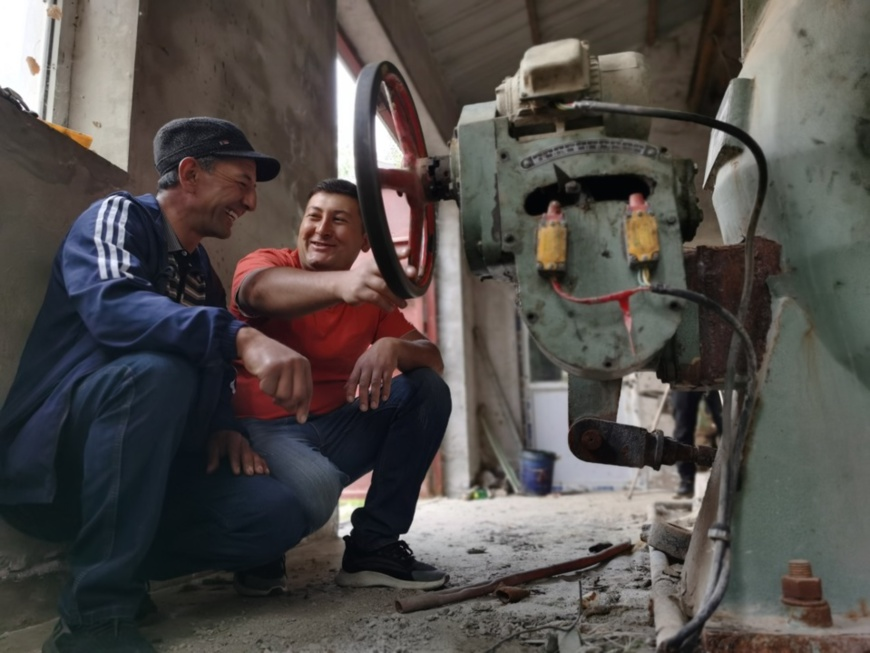 Amirjan (right) checks equipment at a hydropower station in Datong Township with his coworker on June 28. Photo by Li Ya'nan/People's Daily Online