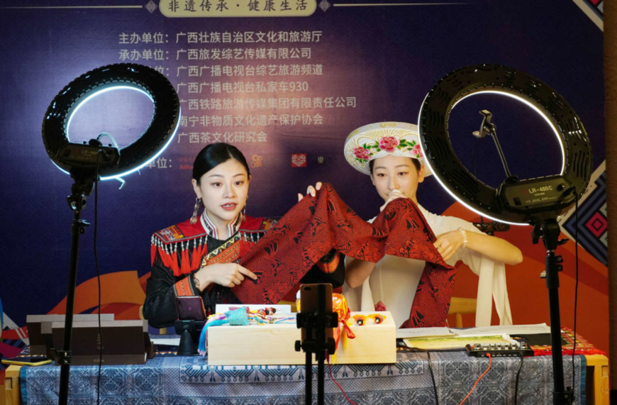 Two women of ethnic minority groups in Nanning, capital of south China's Guangxi Zhuang Autonomous Region, promotes Zhuang brocade, a cultural creative ICH product during the first ICH-themed shopping festival held in the city, June 6. (Photo by Yu Xiangquan/ People's Daily Online)