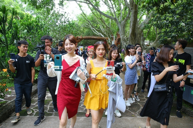 Photo taken on June 25 shows popular livestreaming hosts introducing a scenic spot in Haikou, capital of South China's Hainan Province. (Photo by Zhang Mao/People's Daily Online)
