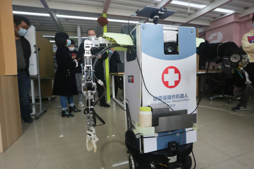 An anti-epidemic teleoperation robot developed by the College of Artificial Intelligence under China's Nankai University displays how it works, April 1. The robot can be controlled by mobile phones, and is able to measure temperature, serve as a hospital guide, disinfect, and transfer samples. Besides, it can also inspect the wards with the cameras installed, and help the doctors launch remote consultation. Photo by Liu Dongyue/ People's Daily Online