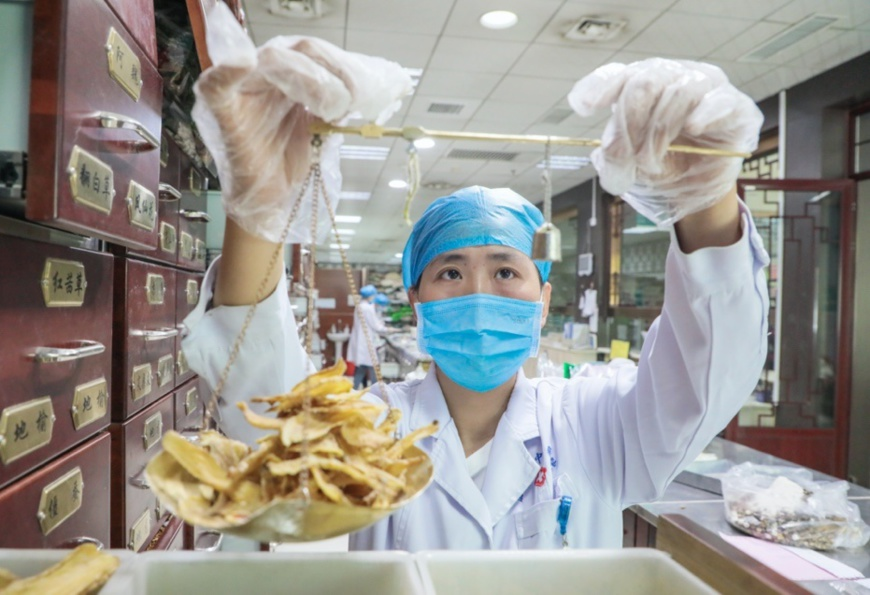 TCM doctor Li Xiaxia with Tengzhou Hospital of TCM, east China's Shandong province weighs TCM herbs, May 7. Photo by Song Haicun/ People's Daily Online
