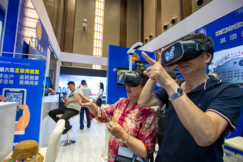On July 31, citizens experience simulated operating rooms of Internet hospitals through VR glasses at an exhibition centered around new infrastructure application scenarios in Nantong, east China's Jinagsu province. (By Zhai Huiyong, People's Daily Online)