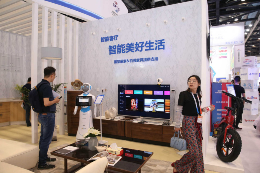 Photo taken on May 29, 2019 shows visitors at a smart living room prototype during the 2019 China International Fair for Trade in Services. (Photo by Chen Xiaogen/People's Daily Online)