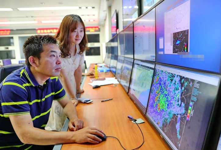 On July 17, an engineer at the meteorological bureau of Qinhuangdao, North China's Hebei Province, monitors meteorological data to help prevent flood. Photo by Cao Jianxiong/People's Daily Online