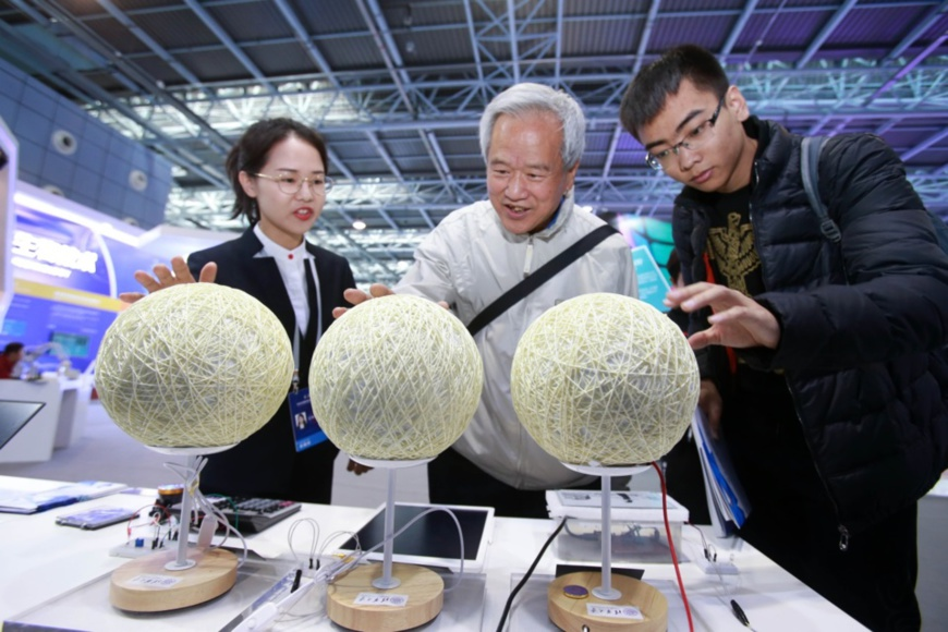 A staff member (L1) introduces vapor power generation at the Zhongguancun International Frontier Science and Technology Achievements Exhibition held at the Zhongguancun Exhibition Center, Zhongguancun Science Park, Beijing. Photo by Chen Xiaogen/People's Daily Online