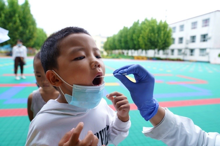 A child is taking the COVID-19 nucleic acid testing in North China's Hebei Province, Xingtai City on August 24. Photo by Hu Liangchuan/People's Daily Online