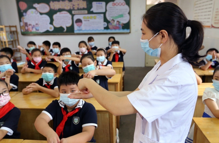 A nurse shows students how to wash their hands at a primary school in Lianyungang, East China's Jiangsu Province on Sept. 1. Photo by Wang Jianmin/People's Daily Online