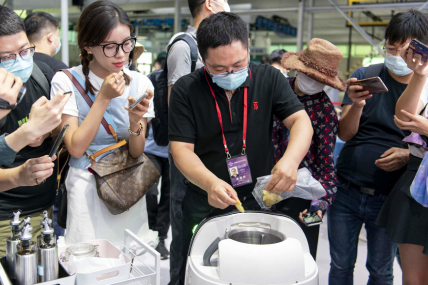 An exhibitor demonstrates the functions of a robot chef to journalists in the service robots exhibition zone of the thematic exhibition pavilion of the 2020 China International Fair for Trade in Services (CIFTIS), Spet.1. (Photo by Weng Qiyu/People's Daily Online)