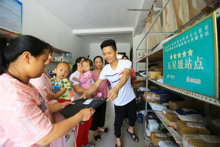 Xin Qingjian (R1), who runs an e-commerce service center in Zhangwei village, Sipu township, Suixi county, Huaibei, east China's Anhui province, hands over a parcel to a villager, June 8. Photo by Wan Shanchao/People's Daily Online