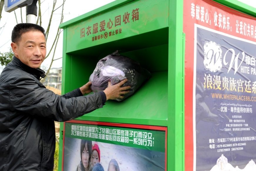A citizen of Yiwu city put a bag of his own old clothes in the old clothes recycling bin on the street. Photo by Zhang Jiancheng, People's Daily Online.