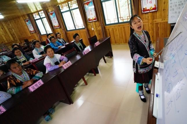 College volunteer Liang Mengxiang teach local women Mandarin in Rongshui Miao autonomous county, Liuzhou, Southwest China's Guangxi Zhuang Autonomous Region on June 3. Photo by Long Linzhi/People's Daily Online