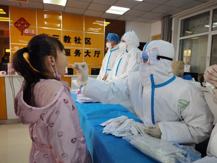 A girl receives COVID-19 nucleic acid test at a designated testing site in Shijiazhuang, north China's Hebei province, Jan. 6. (Photo by Lv Lining/People's Daily Online)
