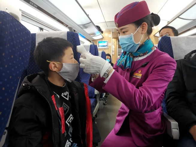 A car attendant checks body temperature of a boy passenger during the Spring Festival travel rush on Feb. 2, 2020. Photo by Hu Zhiqiang/People's Daily Online
