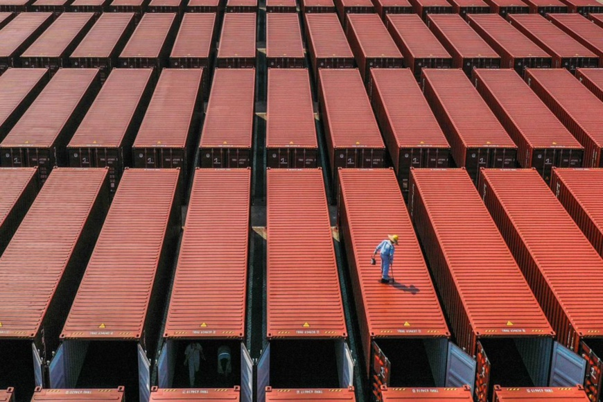 Employees of a container manufacturer paint and check containers in Nansha District, Guangzhou, south China's Guangdong Province, Feb. 3, 2021. (Photo by Qiu Xinsheng/People's Daily Online)