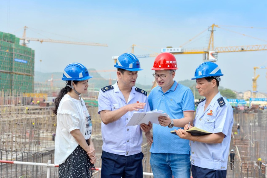 Staff members with the tax bureau of Changxing county, east China's Zhejiang province, interview construction workers to make sure they understand the country's policies on cutting tax and administrative fees, Sept. 11, 2019. (Photo by Tan Yunfeng/People's Daily Online)