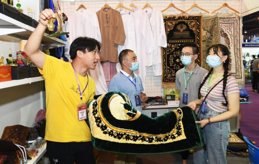 Merchants purchase a batch of carpets scheduled to be exported to Arab countries at the third China (Yiwu) Cross-Border E-Commerce Industrial Belt Expo, Sept.13, 2020. (Photo by Gong Xianming/People's Daily Online)
