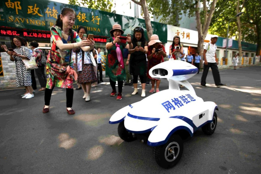 A smart robot patrolling a residential complex in Jinan, capital of east China's Shandong province, attracts the attention of citizens, July 21, 2020. The smart patrol robot can identify hazardous conditions and illegal activities like noise, fire hazard, and illegal parking and send messages to the police of the local community. (Photo by Hao Xincheng/People's Daily Online)
