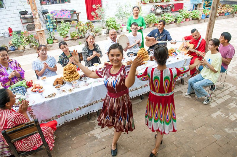 Residents of various ethnic groups celebrate the Corban Festival, one of the major festivals of Muslims, by enjoying traditional food, dancing, and singing in Kuqa city, Aksu prefecture, northwest China's Xinjiang Uygur autonomous region, July 19, 2021. (Photo by Yuan Huanhuan/People's Daily Online)