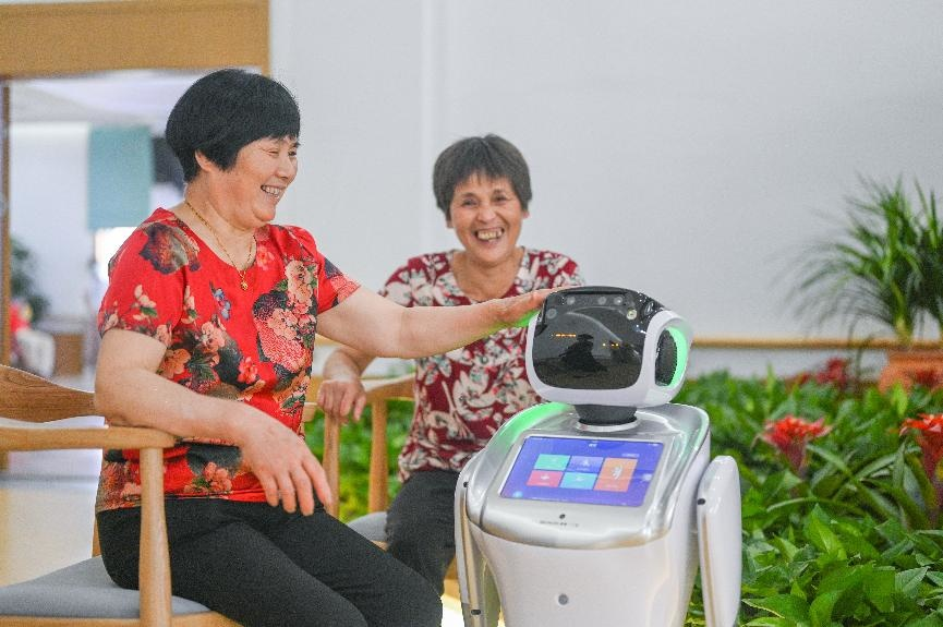 Seniors experience a nursing robot at a nursing home in Huzhou, east China's Zhejiang province, June 2, 2020. (Photo by Liu Chunhui/People's Daily Online)