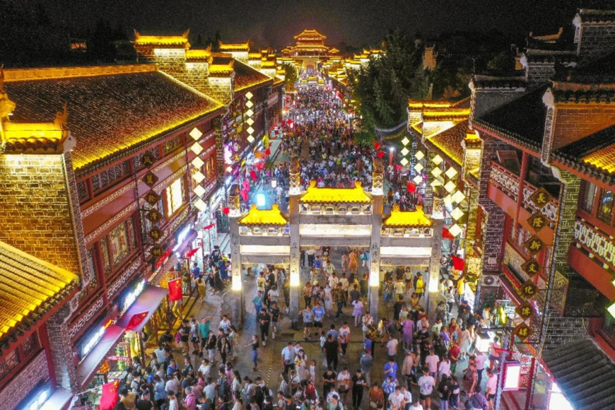 Photo taken on Oct. 3, 2021 shows tourists at the illuminated Xiangyang ancient town, Xiangyang city, central China's Hubei province. (Photo by Yang Dong/People's Daily Online)