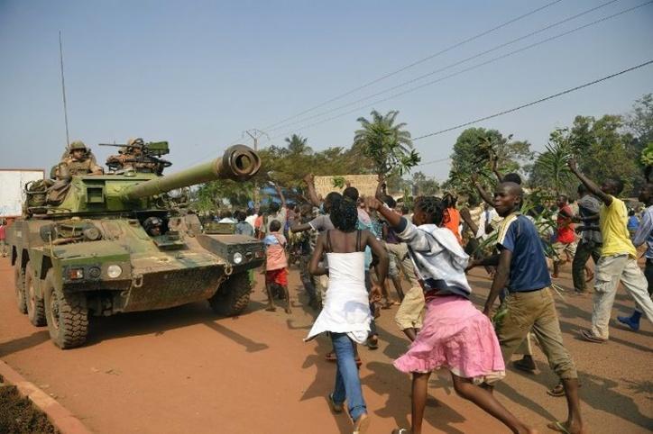 Des manifestants anti-Séléka, hostiles à Michel Djotodia, passent près d'un blindé français le 10 janvier à Bangui. (Photo Eric Feferberg. AFP)