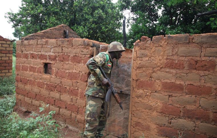 Un Casque bleu africain inspecte une maison abandonnée dans l'un des nombreux villages le long d'une route au sud de Bossangoa, en République centrafricaine. Photo: IRIN/Hannah McNeish
