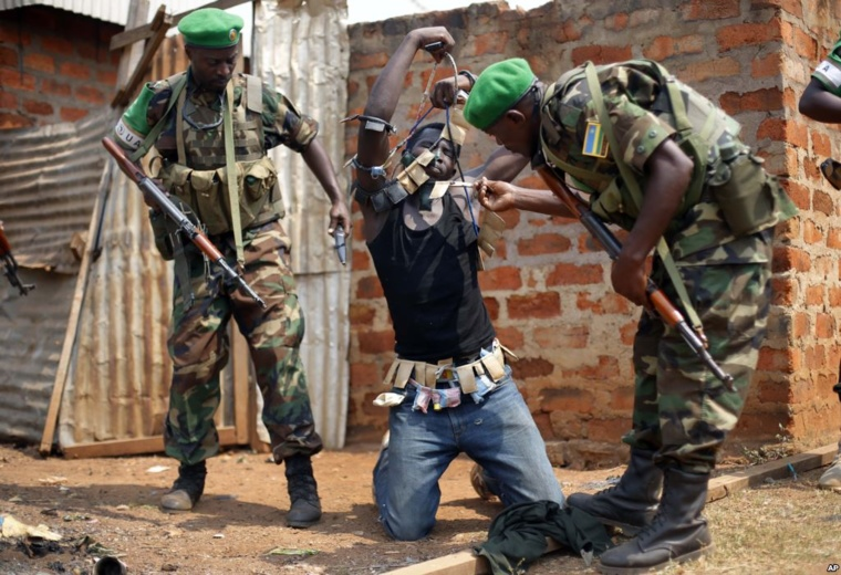 Rwandan African Union peacekeepers remove the lucky charms from a suspected Anti-Balaka Christian man who was found with a rifle and a grenade following looting in the Muslim market of the PK13 district of Bangui, Central African Republic.