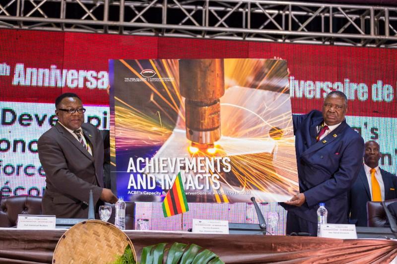 """Le Vice-président de la République du Zimbabwe, Phelekezela Mphoko à (droite) présente le livre commémoratif intitulé """"ACBF in Action, 25 years of capacity development impact across Africa""""."""