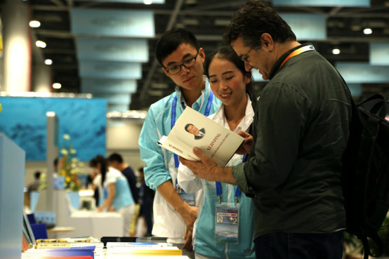 The news center of the G20 Hangzhou Summit begins operation on Sept.1. A foreign journalist is inquiring about the book Xi Jinping: The Governance of China at the booth of the news center. (Jiao Xiang from People's Daily)
