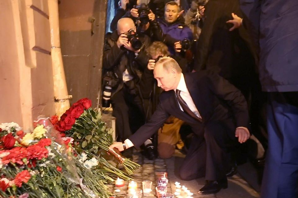 Vladimir Poutine dépose des fleurs pour les victimes de l'explosion dans le métro de Saint-Pétersbourg, le 3 avril 2017. STR - AFP