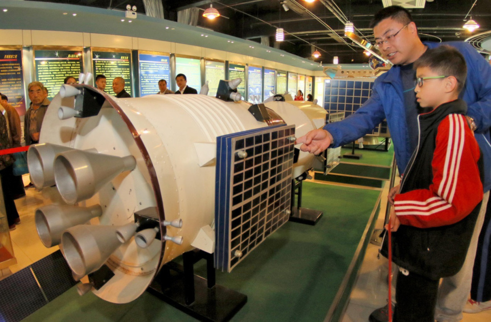 """In April 2017, citizens are watching """"Shenzhou"""" spacecraft model, learning the knowledge of space and the achievements of Chinese space development in Yantai, Shandong province. Photo from People's Daily website"""