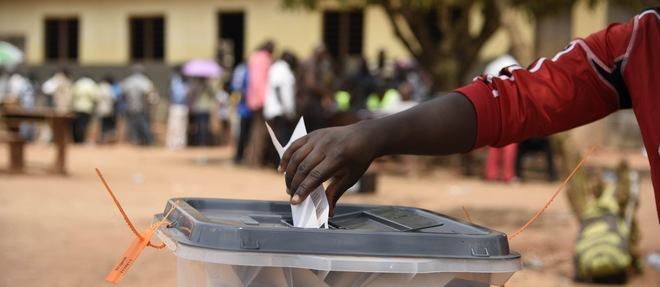 En Ouganda, dans le district de Wakiso, le 19 février 2016, un homme met son bulletin dans l'urne. © AFP / Isaac Kasamani
