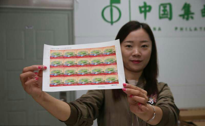 A postal staff shows the commemorative stamps for the 19th CPC National Congress on Oct. 17 in Leshan, southwest China's Sichuan Province. (Photo from People's Daily Online)