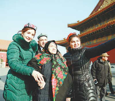 Great granddaughter of Kurban Tulum (fourth left), a Uygur patriot, accompanies a 106-year-old senior Uyghur (third left) to visit the Tian'anmen Rostrum in Beijing, January 19, 2016. The story of Kurban Tulum riding a donkey from Xinjiang to Beijing in the 1950s is widely known in Xinjiang. (Photo by People's Daily)