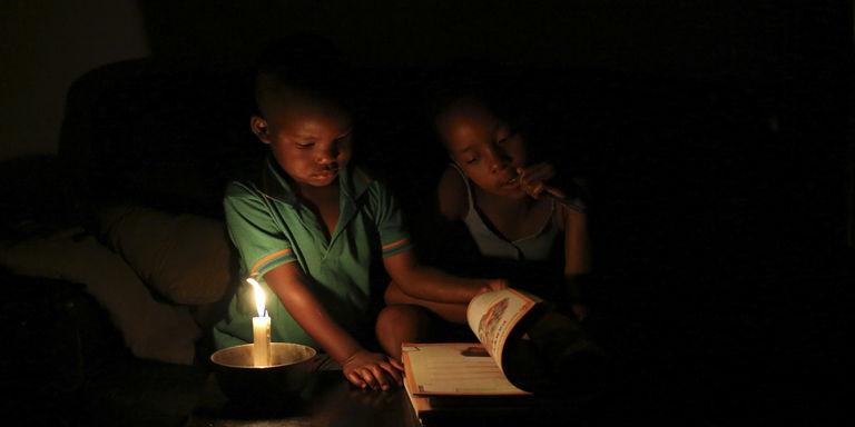 A Soweto, en Afrique du Sud, Sinovuyo Bhungane, 9 ans, fait ses devoirs à la bougie. CRÉDITS : REUTERS