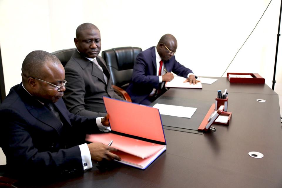 Valentin Oko, (extrême droite) signant le parapheur de la passation de service