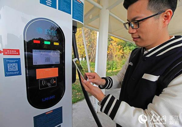 A motorist tests the quick-charging service for electric vehicles at an expressway service area in Ningbo, Zhejiang Province. The service has nearly achieved full coverage in the province. (Photo by People's Daily Online)