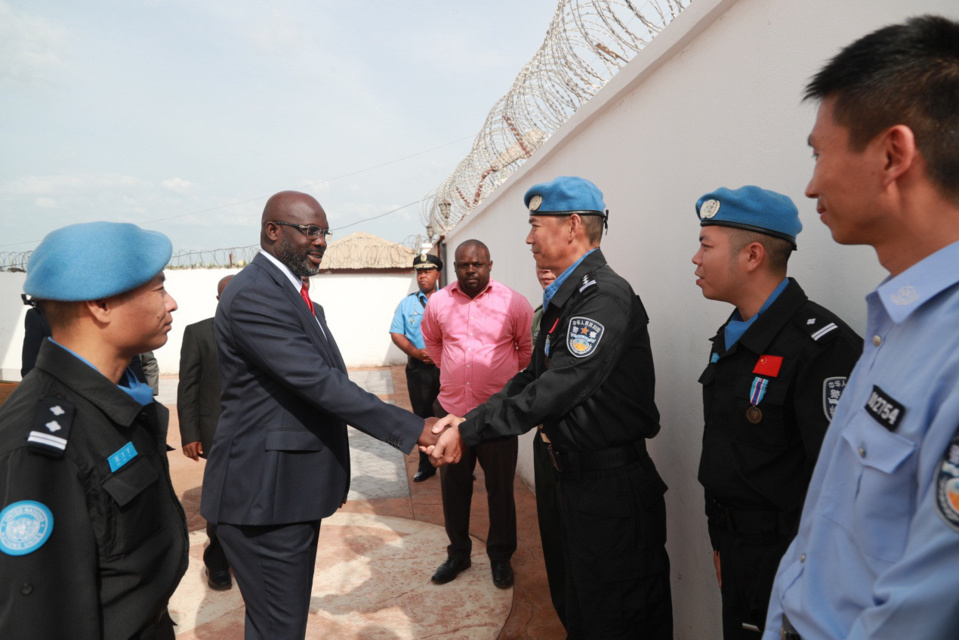 Liberian President George Weah (second from left) shakes hands with a member of the fifth Chinese peacekeeping police team in Monrovia, capital of Liberia. (Photo by Zhao Xiaoxin from People's Daily)