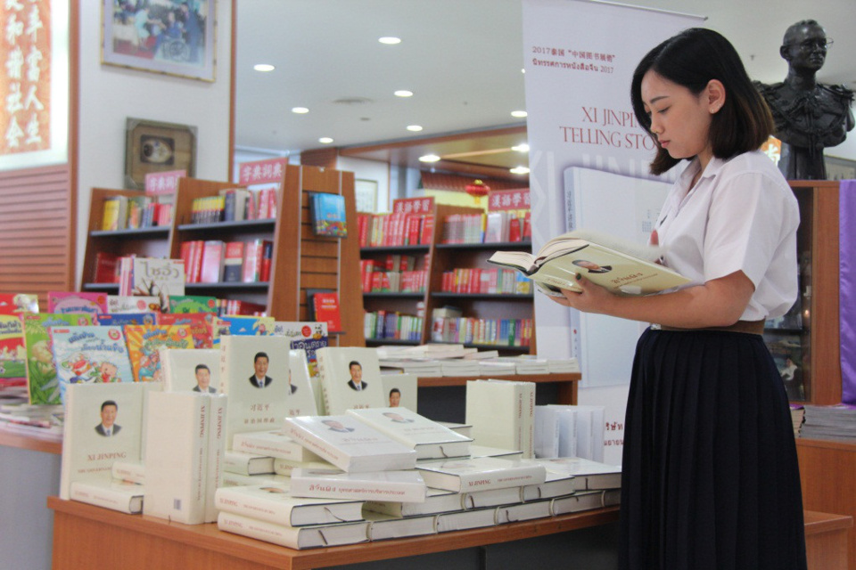 A Thai student leafs through Xi Jinping: The Governance of China, the collected speeches, talks, interviews, notes and letters of the Chinese leader. (Photo by Sun Guangyong from People's Daily)