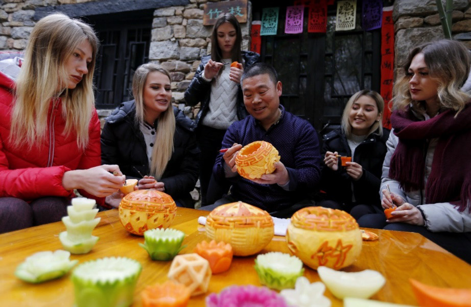 Foreign tourists learn to make turnip lanterns in Zhuquan Village, Yinan County, east China's Shandong province. (Photo from CFP)