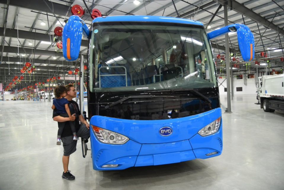 A US father taking his daughter to learn about an electric bus manufactured by BYD, October 6, 2017. On that day, the North American factory of BYD saw the completion ceremony of its third-phase extension project in Lancaster, Southern California, US. (Photo by Zhang Niansheng from People's Daily)