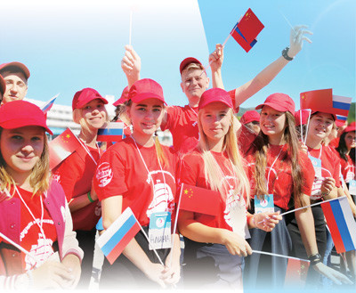 Russian students hold Chinese and Russian national flags to welcome Chinese guests. (Photo by Qu Pei from People's Daily)